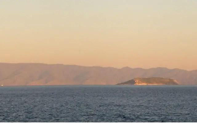 Blick auf eine Insel im Marmarameer. Aufgenommen von einem Boot. Dahinter ist das Festland zu sehen. Das Meer ist dunkelblau. Die Sonne geht unter und den Himmel ist rötlich.