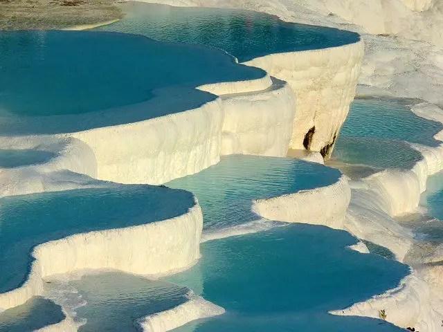 In den weißen Kalterrassen fängt sich das Wasser der Thermalquellen von Pamukkale. Es ist hellblau und fließt über mehrere Terrassen bis in das Tal hinab.