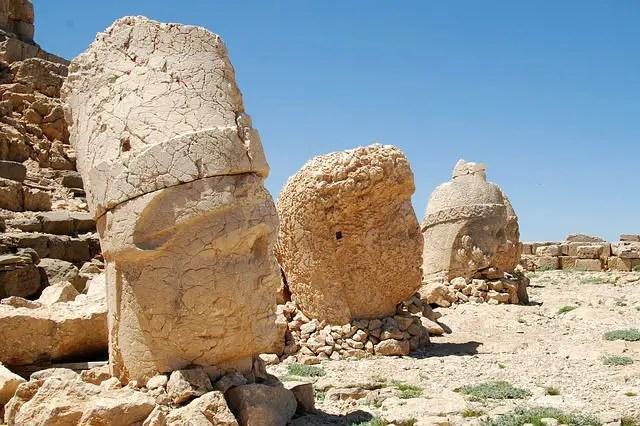 Die über 2 Meter hohen in Stein gemeißelten Köpfe von antiken Göttern. Die Steine sind in Sandfabre gehalten.