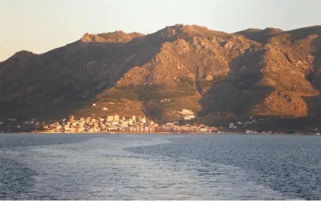 Foto eines Dorfes auf der Marmara Insel. Aufgenommen von einer abfahrenden Fähre. Das Wasser ist dunkelblau. Es sind die am Heck ausgehenden Wellen des Schiffes zu sehen. Die Sonne geht unter. Der Himmel ist rötlich gefärbt. Die Insel hat eine steile Küste. Sie ist grün bewachsen.