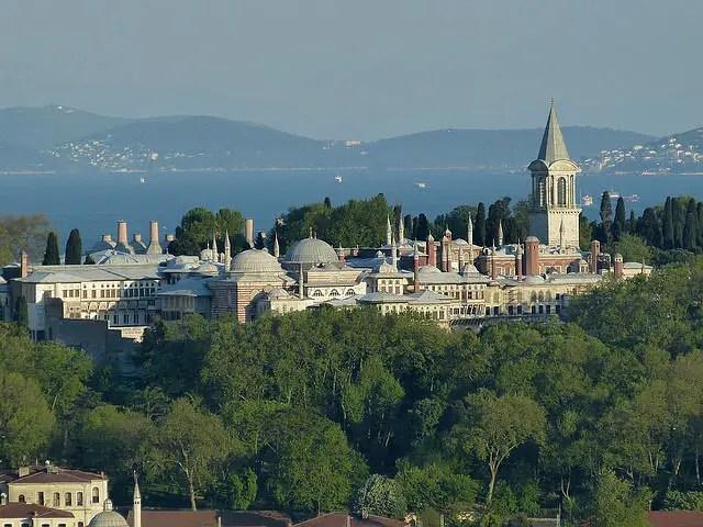 Panoramablick von einem gegenüberliegenden Hügel auf den Topkapi Palast. Davor sind ein paar grüne Bäume zu sehen. In dem kleinen Wald stehen die Gebäude der alten osmanischen Palastanlage. Dahinter ist der Bosporus zu sehen.
