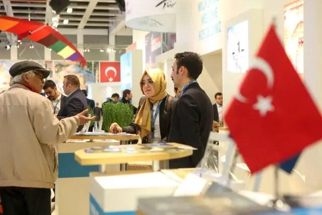 Stand in der Türkei Halle der Messe. Im Vordergrund ist eie türkische Flagge zu sehen, ein Mann und eine Frau mit Kopftuch.