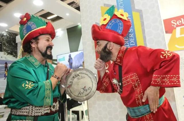 Zwei Türken in traditioneller Tracht am Stand von Bursa. Der eine trägt rote Kleidung und der andere grüne. Beide tragen einen Hut mit Blumen darauf.