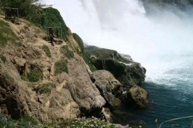 Vergrößertes Bild eines Anglers der neben dem Wasserfall fischt. Er wirkt im Vergleich zum herunterfallenden Wasser winzig klein.