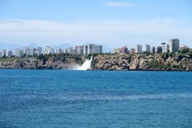 Düden Wasserfall aus zwei Kilometer Entfernung vom Yakamoz Strand in Antalya aufgenommen. Die hinter dem Wasserfall gebauten Hochhäuser wirken gleich hoch wie die Klippen