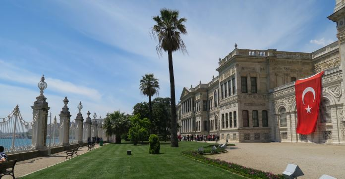 Die zum Bosporus ausgerichtete Seite des Dolmabahce Palast. Es ist eine Parkanlage mit kurz geschnittenem Rasen, Palmen, Sträuchern und dem weißen Palastgebäude zu sehen. Ein weißer Eisenzaun grenzt den Palast vom Meereswasser ab.