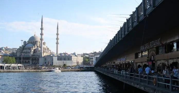 Aufnahme von der Galatabrücke Richtung Yeni Camii in Istanbul. Auf der unteren Seite der Brücke sind Restaurants, auf der oberen Seite ist die Fahrbahn für Autos. Darauf stehen ein paar Fischer.