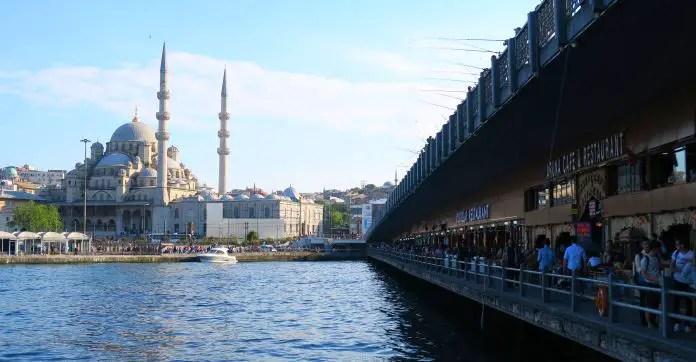 Restaurnts auf der Galata Brücke auf der östlichen Seite. Die Brücke hat zwei Sttockwerke. Unten sind Restaurants und oben ist die normale Fahrtbahn der Straße. Es stehen unten und oben Fischer. Rechts auf dem Bild ist eine Moschee zu sehen.
