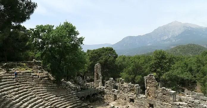 Blick von den Ruinen der oberen Ränge des Amphitheaters von Phaselis auf den im Hintergrund gelegenen Berg Tahtali und die dazwischen liegenden Wälder