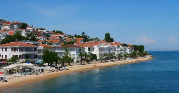 Strand mit Sonnenliegen und Sonnenschirmen. Dahinter sind weiße Häuser mit roten Dachziegeln zu sehen. Auf der Inel stehen Pinien und Palmen. Am rechten Bildrand ist die Sykline von Istanbul erkennbar.