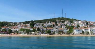 Aufnahme der Küste und des Strandes auf der Insel Kinali. Augenommen von einer Fähre etwa 100 Meter vor der Küste. Es sind im Hintergrund weiße Strandhäuser an einem Hang zu sehen und ein grüner Wald.