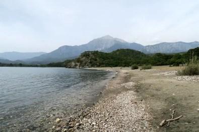 Blick vom Strand auf den im Hintergrund gelegenen Berg Tahtali. Dazwischen sind Wälder zu sehen.
