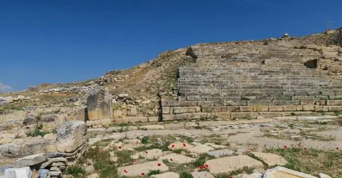 Treppen zur Kreuzigungskirche, rechts nebem dem Grab von St. Phillip. Am Boden sind alte Steinplatten und ein paar rote Blumen zu sehen.