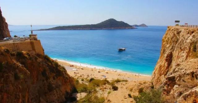 Foto von der Straße oberhalb der Steilküste auf den darunterliegenden Sandtrand Kaputas Beach. Im Hintergrund ist das türkisblaue Meer und kleine Inseln zu sehen.