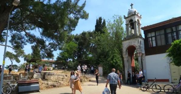 Menschen und das kleine Turm des Klosters auf der Inselspitze