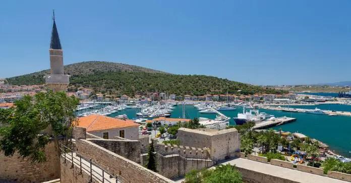 Blick auf den Hafen von Cesme an der türkischen Ägäisküste. Türkisblaues Meereswasser der Ägäis und viele weiße Yachten sind hinter der Altstadt von Cesme zu sehen.