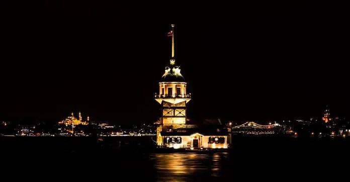 Der hell erleuchtete Leanderturm im Bosporus mit der europäischen Seite von Istanbul im Hintergrund.