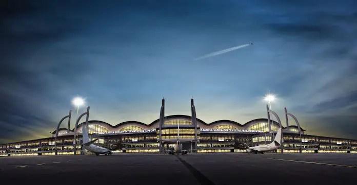 Flughafen Istanbul Sabiha Gökcen in der Nacht von der Parkbuchten der Flugzeuge aus augenommen. Mit einem fliegenden Flugzeug über dem Terminalgebäude.