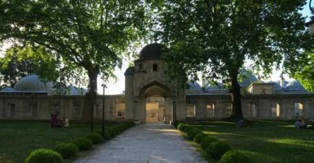 Innenhof der Süleymaniye Moschee mit dem Eingangstor der umliegenden Mauer und einer Rasefläche mit Bäumen und Sträuchern