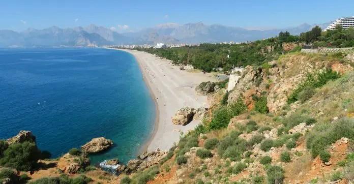 Konyaalti Strand in Antalya. Blick vom östlichen Strandende Richtung Taurusgebirge. Es sind wenige Badegäste am Strand zu sehen.