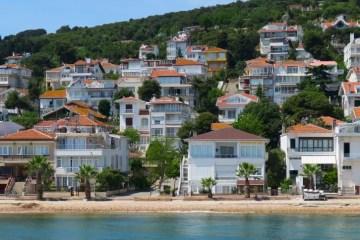 Strand der Insel Kinali in Istanbul: Aufgenommen von einer Fähre mit Blick auf die Strandvillen in weißer Farbe mit roten Dächern und den davor liegenden Sandstrand