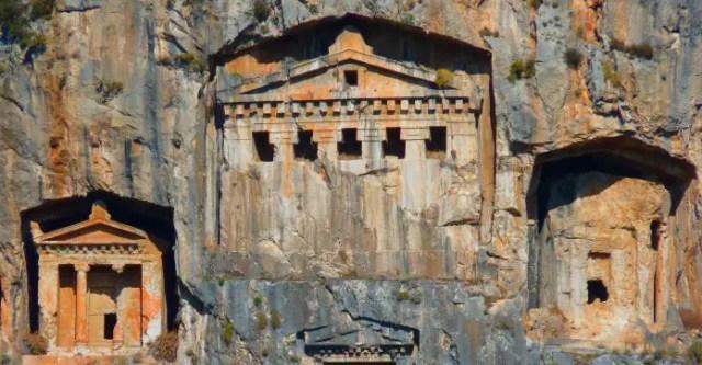Das größte Grab mit mehreren Fenstern und zwei daneben liegenden karischen Felsengräbern an einem steilen Berghang.