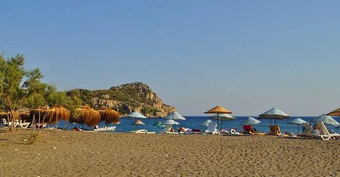 Der Strand von Datca. Reisende liegen auf Sonnenliegen, unter Sonnenschirmen. Der Blick geht Richtung Meer.