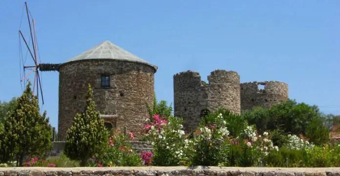 Eine intakte Windmühle hinter kleinen Sträuchern. Im Hintergrund sind die Ruinen mehrer Windmühlen zu sehen.