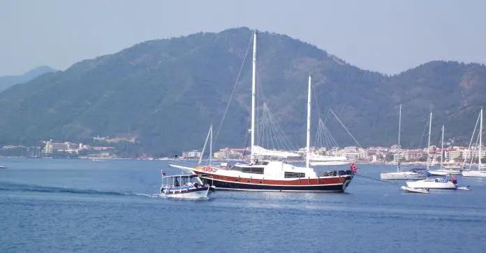 Ein weißes Gulet und weiße Segelschiffe, in der Bucht und dem Hafen vor Marmaris. Dahinter sind die Berge an der Küste zu sehen.