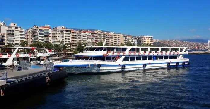 Eine weiße Fähre mit Passagieren und türkischen Flaggen an Deck legt am Hafen an.