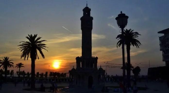 Der Uhrtrum von Izmir bei Sonnenuntergang. Daneben stehen Palmen und das Meer ist im Hintergrund zu sehen.