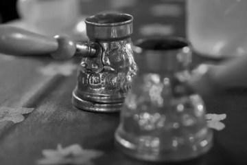 Zwei Cezve stehen auf einem Holztisch. Das Foto ist in Schwarz-Weißer Farbe gehalten.