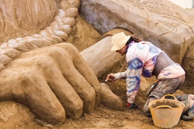 Ein Künstler arbeitet gerade an einer Sandskulptur der nordischen Götterfigur Thor.