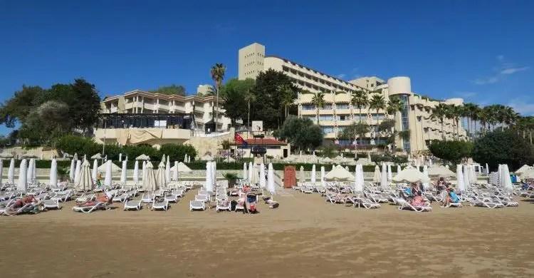 Eine Clubanlage steht am öffentlichen Strand in der Türkei. Dort sind Liegestühle und Sonnenschirme mit Badegästen zu sehen.