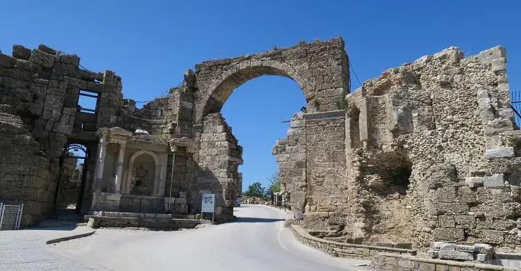 Die Ruinen der alten Stadtmauern und des Stadtores von Side. Es ist nur noch der Torbogen und ein Teil der umliegenden Mauern erhalten.