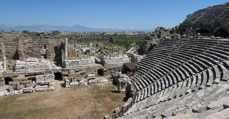 Der Ausblick vom obersten Sitzrang des Theaters von Side auf die hinter dem Bunenhaus liegenden Ruinen und die Berge des Taurus im Hintergrund.