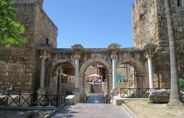 Das aus drei Torbögen und Marmor bestehende Hadrianstor führt in die Innenstadt von Antalya. Es ist von zwei hohen Türmen und Palmen umgeben.