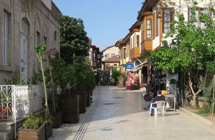 Eine schmale, gepflasterte Straße ist mit Blumentöpfen umgeben. Es stehen alte Osmanische Steinhäuser mit Holzbalkonen direkt an der Straße.