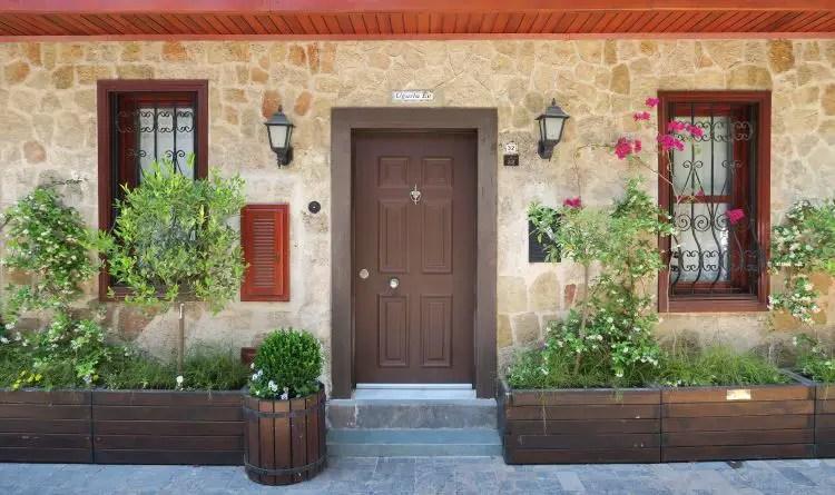 Der Eingang eines aus Steinen und Holz gebauten osmanischen Hauses in Antalya. Es stehen Blumen und Sträucher davor. Das Haus sieht ordentlich und sauber aus.