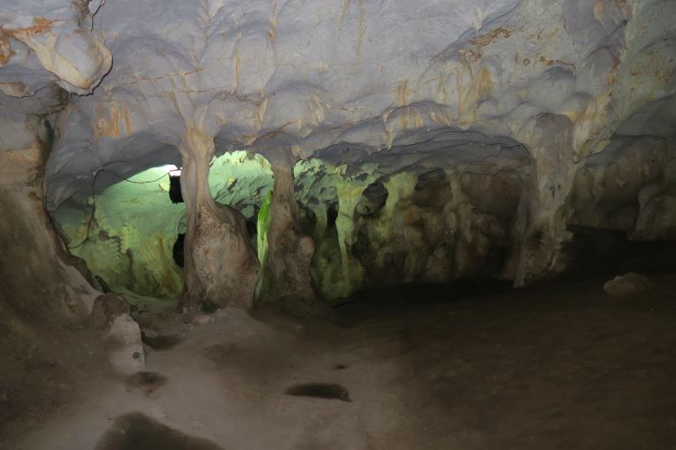 Der Weg führt in die mit grünlichem Licht beleuchtete Karain Höhle hinein.