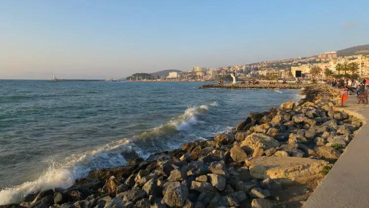 Der Hafen von Kusadasi im Frühling. Die Sonne geht unter, es spazieren Menschen am Hafen entlang oder sitzen auf Bänken. Die Sonne scheint, der Himmel ist blau.