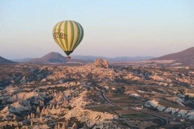 Der Blick aus einem Heißluftballon auf einen anderen Ballon und die Festung Uchisar in Kappadokien.