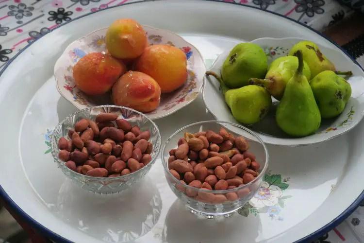 Auf einem Teller liegt frisches Obst und frische Nüsse.