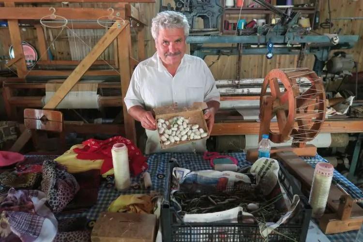 Ein Mann hält einen Karton mit Seidenkokons und Raupen in seiner Hand.