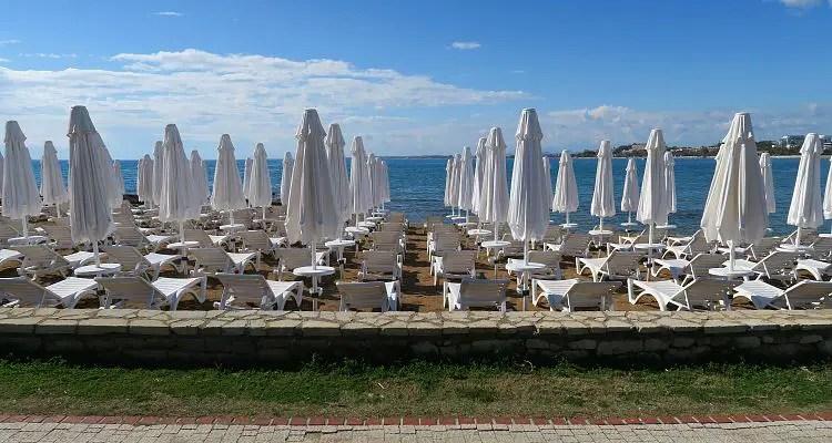 Dutzende, weiße Liegestühle mit weißen Sonnenschirmen stehen am Meer in Side, in der Türkei.