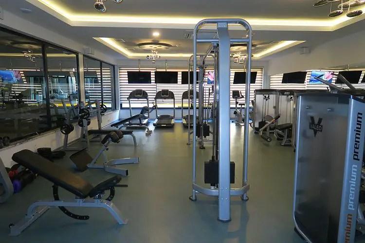 Fitnessraum mit Fitnessraumgeräten und Hanteln.