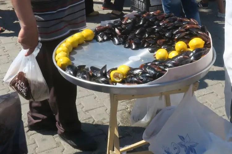 Midye Dolma liegen auf einer kleinen Silberplatte zusammen mit Zitronen.