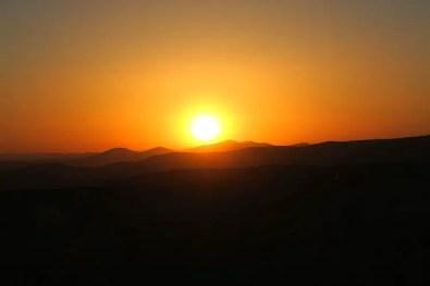 Die Sonne geht mit einem orangenen Licht hinter den Bergen von Kappadokien auf.