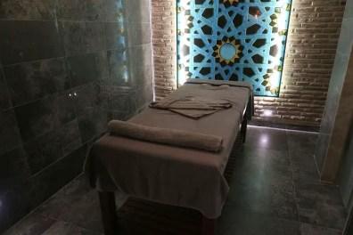 Eine Massageliege in einem abgedunktelten Massageraum mit orientalischer Verzierung.