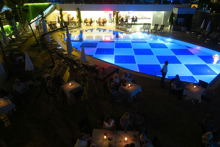 Der Pool mit Tischen und Sesseln am Abend.